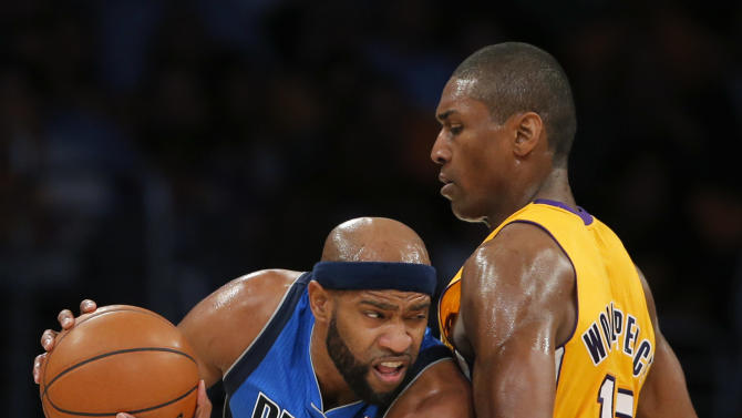 Dallas Mavericks' Vince Carter, left, drives against Los Angeles Lakers' Metta World Peace in the first half of an NBA basketball game in Los Angeles, Tuesday, Oct. 30, 2012. (AP Photo/Jae C. Hong)