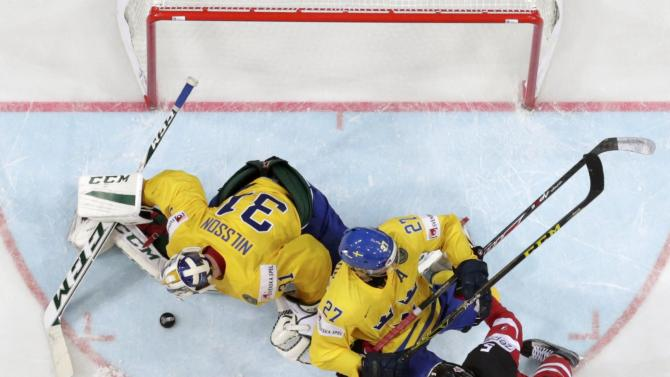 Canada's Ekblad challenges Sweden's Ericsson and goaltender Nilsson during their Ice Hockey World Championship game at the O2 arena in Prague
