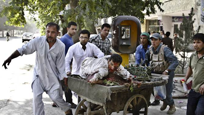 Afghans rush a wounded man to receive treatment, after a suicide car bomber struck outside the Afghan Supreme Court in Kabul, Afghanistan, Tuesday, June 11, 2013. The suicide car bomber killed more than a dozen and wounded tens, police and health officials said. The car bomb exploded outside the court's back entrance as employees were leaving for the day and as cars belonging to staff were driving out of the back gate, said police officer Jahn Agha. (AP Photo/Ahmad Jamshid)