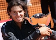 Spain&#39;s Rafael Nadal poses with his trophy after winning the Monte-Carlo ATP Masters Series Tennis Tournament final against Serbia&#39;s Novak Djokovic on April 22, in Monaco. The accolades continued to rain down Monday on Nadal after the Spaniard made tennis history at the weekend by winning an eighth straight Monte Carlo title by beating world number one Novak Djokovic 6-3, 6-1