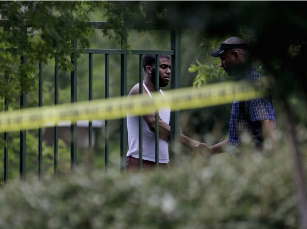 A man, at left, is greeted by an investigator inside a housing complex at the scene of a shooting, Sunday, June 10, 2012, in Auburn, Ala. Auburn Police Chief Tommy Dawson said authorities responded du