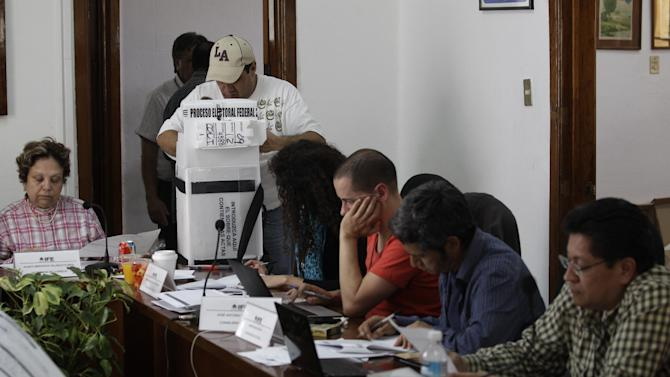Election officials and party representatives begin the computation of ballot boxes at an electoral institute district council in Mexico City, Wednesday July 4, 2012. The computation is done to determine which ballot boxes used in last Sunday's general elections will be recounted in front of party representatives. (AP Photo/Dario Lopez-Mills)