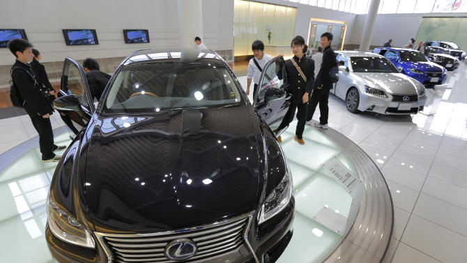 FILE - In this Wednesday, May 8, 2013 file photo, school boys look at Toyota Lexus LS600hL displayed at Toyota Motor Corp.'s showroom Toyota Mega Web in Tokyo. Toyota shrugged off China sales woes to stay the world's top selling automaker for the first half of this year, outpacing U.S. rival General Motors Co., which boasted such bragging rights for seven decades until 2008. The Japanese automaker sold 4.91 million cars and trucks around the world for the January-June period, down 1.2 percent from the previous year, according to numbers it released Friday, July 26. (AP Photo/Itsuo Inouye, File)