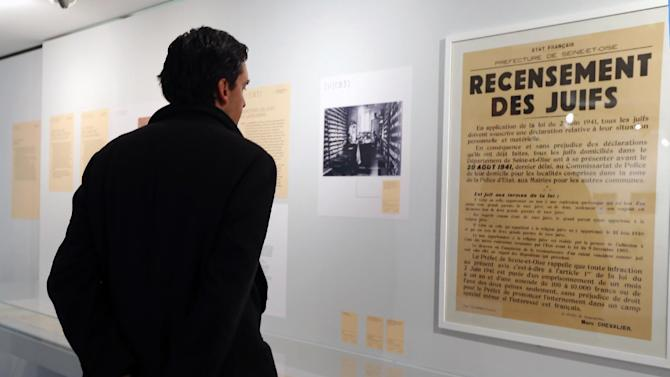 """A man looks at a poster reading """"Census of Jews"""" displayed in an exhibition at the Shoah Memorial in Paris, Tuesday, Feb. 12, 2013. The French state prepares to give back seven stolen Nazi-era paintings - 4 of which are in the Louvre - to two Jewish families, after a decade-long tug of war. It ends years of struggle for the two families, whose claims were all validated by the French prime minister last year. (AP Photo/Jacques Brinon)"""
