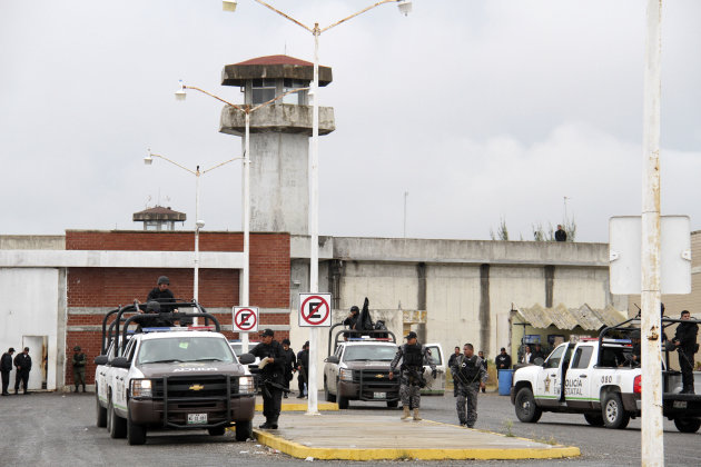 Police stand outside the Altamira prison, in the town of Altamira, Mexico, Thursday Jan. 5, 2012, after a prison riot broke out leaving 31 inmates dead. Mexican authorities have detained 20 inmates for alleged involvement in the prison riot, in a state bordering Texas and are investigating whether prison staff were also responsible. A fight ensued when one cell block invaded another Wednesday afternoon, causing a brawl among prisoners armed with makeshift knives, clubs and stones, said Morelos Canseco, interior