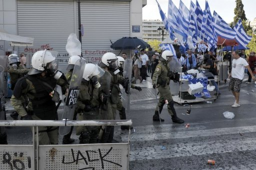 <p>Protesters throw trash at riot police in Athens, during a protest march marking a 24-hours general strike on October 18. Eurozone leaders on Friday hailed Greece's achievements in carrying out reforms aimed at getting its economy back on track and urged Athens to keep up efforts to stay in the eurozone.</p>