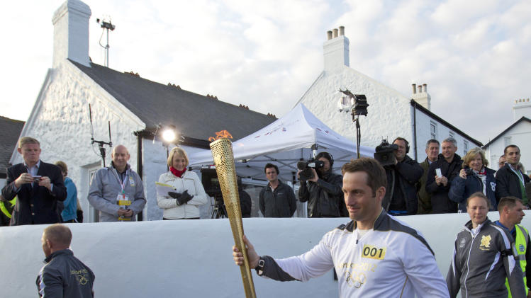 British Olympic sailing hero and three time gold medalist Ben Ainslie walks past the media as he holds the Olympic torch at the official start of the London 2012 Olympic games torch relay at Land's End, south west England, Saturday, May 19, 2012. The torch relay will travel some 8,000 miles round the British Isles on its way to the Olympic Stadium in London for the opening of the summer games on July 27.(AP Photo/Alastair Grant)