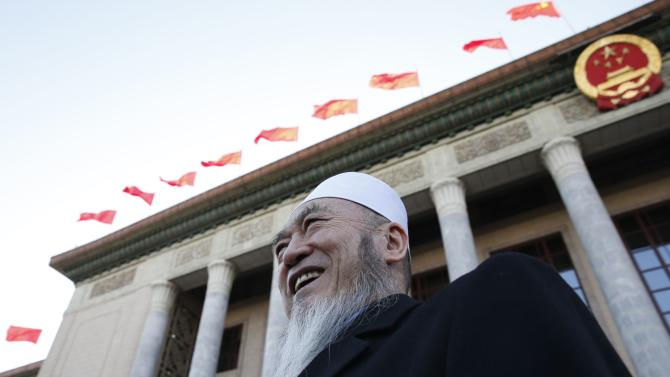 A delegate smiles in front of the Great Hall of the People after the opening session of Chinese People's Political Consultative Conference at Tiananmen Square in Beijing