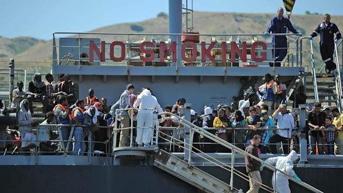 "Immigrants are transferred from the tanker ""Torm Lotte"" to the tug boat ""Grifone"" near Messina following a rescue operation on July 20, 2014"