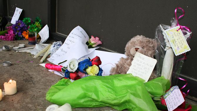 A memorial for Amanda Connors sits outside the salon she managed Wednesday, Sept. 12, 2012, in Sioux Falls, S.D.  Police say Connors was killed trying to protect an employee and her two children from Tyrone Smith who was upset about a domestic violence arrest and protection order. Smith was found dead of a self-inflicted gunshot wound. (AP Photo/Kristi Eaton)