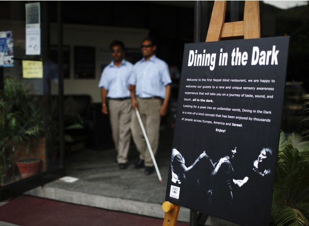 Visually impaired waiters walk out of Nepal's first blind restaurant as they wait for customers in Kathmandu