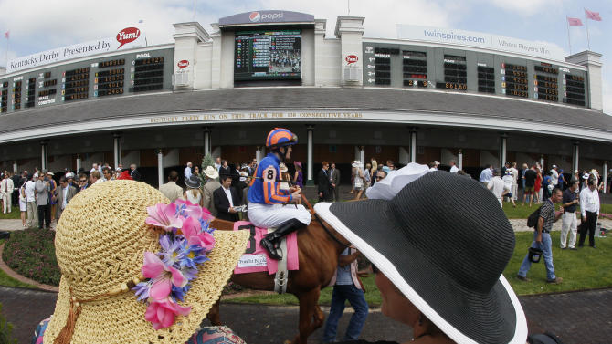 Race goers watch as jockey Colm O'Donoghue rides Revolving through the paddock before the third race at the 138th Kentucky Derby horse race at Churchill Downs, Saturday, May 5, 2012, in Louisville, Ky. The Run for the Roses draws them to Churchill Downs. But what race goers wear is as much a spectacle in itself. (AP Photo/Mark Humphrey)