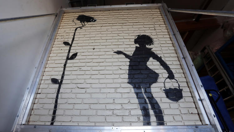 "FILE - This Dec. 4, 2013 file photo shows ""Flower Girl,"" a stencil on a massive brick wall by popular street artist Banksy, is displayed in a warehouse in Los Angeles. The mural stenciled on the side of a Hollywood gas station five years ago has fetched more than $200,000 at a Beverly Hills auction on Thursday Dec. 5, 2013. (AP Photo/Reed Saxon,File)"