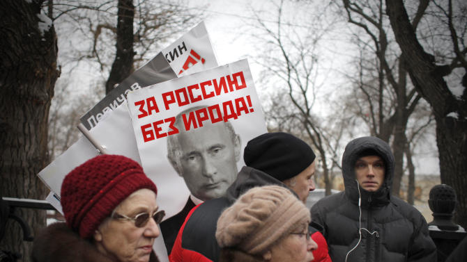"""People carry a posters of Russian President Vladimir Putin with the words reading """"For Russia without Herod!"""" during a protest rally in Moscow, Russia, Sunday, Jan. 13, 2013. Some thousands of people are gathering in central Moscow for a protest against Russia's new law banning Americans from adopting Russian children, some carrying posters of President Vladimir Putin and members of Russia's parliament who overwhelmingly voted for the law last month, with the word """"Shame"""" written in red over the faces and the demonstrators proclaim that Sunday's demonstration is a """"March Against the Scum"""" who enacted the law. The reference to Herod in this poster refers to the Biblical ruler who murdered members of his own family and is guilty of initiating the killing of infants in Bethlehem during the time of Jesus. (AP Photo/Alexander Zemlianichenko)"""