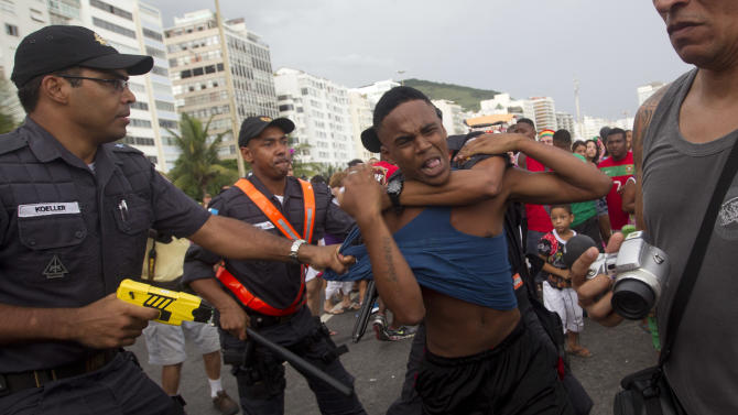 """Brazil's police officers detain an alleged thief during the """"Blocao"""" dog carnival parade in Rio de Janeiro, Brazil, Sunday, Feb. 3, 2013. According to Rio's tourism office, Rio's street Carnival this year will consist of 492 block parties, attended by an estimated five million Carnival enthusiasts. (AP Photo/Silvia Izquierdo)"""