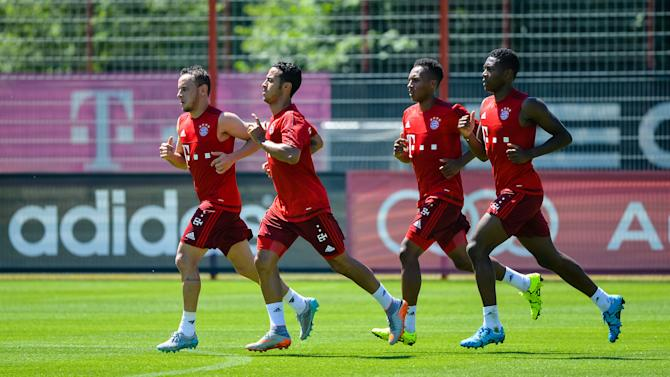 From left: Munich's Rafinha ,Thiago, Julian Green and David Alaba warm up during a practice session of the squad of   Bayern Munich Bundesliga soccer club, in Munich, southern Germany, Wednesday July 1, 2015.  (Matthias Merz/dpa via AP)