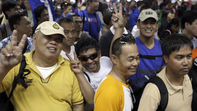"Overseas Filipinos who were working at the sprawling oil field in Algeria which was attacked by terrorists, flash the ""V"" sign as they queue up at the Philippine Immigration upon arrival Sunday, Jan. 20, 2013 at the Ninoy Aquino International Airport in Manila, Philippines. The Department of Foreign Affairs in their statement, said that 39 Filipino workers, out of the 52 accounted for following the Algerian hostage crisis, arrived after being evacuated from Algeria via Palma de Mallorca in Spain. The workers claimed they were hundreds of kilometers away from the hostage-taking site but ordered evacuated. (AP Photo/Bullit Marquez)"