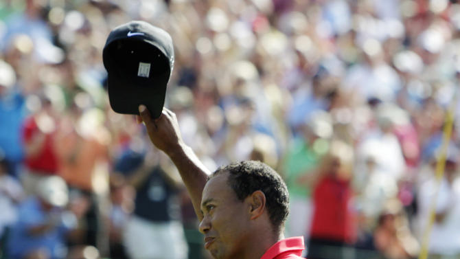 Tiger Woods waves to the crowd after making a birdie putt on the 18th hole during the final round of the Memorial golf tournament, Sunday, June 3, 2012, in Dublin, Ohio. Woods birdied three of his last four holes to win the Memorial and match tournament host Jack Nicklaus with his 73rd title on the PGA Tour. (AP Photo/Jay LaPrete)