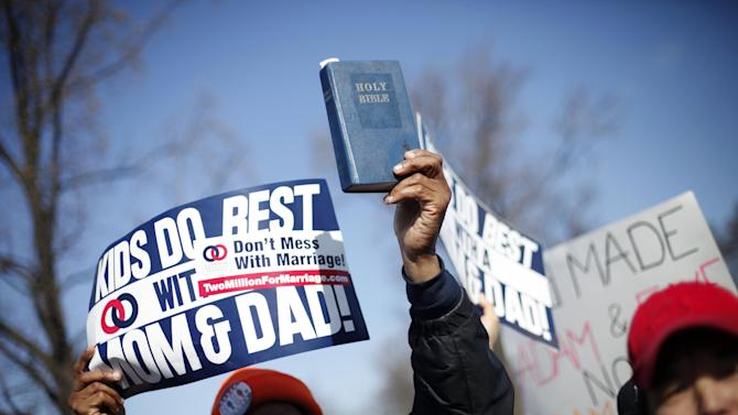 A demonstrator holds a bible while marching outside the Supreme Court in Washington, Tuesday, March 26, 2013, as the court heard arguments on California's voter approved ban on same-sex marriage, Proposition 8. The Supreme Court waded into the fight over same-sex marriage Tuesday, at a time when public opinion is shifting rapidly in favor of permitting gay and lesbian couples to wed, but 40 states don't allow it.  (AP Photo/Pablo Martinez Monsivais)