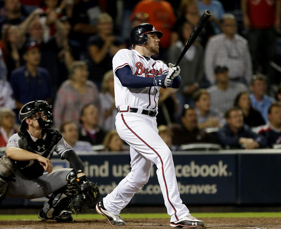 Atlanta Braves' Freddie Freeman watches his two-run home run in the ninth inning against the Miami Marlins in a baseball game Tuesday, Sept. 25, 2012, in Atlanta. The Braves won 4-3, clinching a playoff spot. (AP Photo/David Goldman)