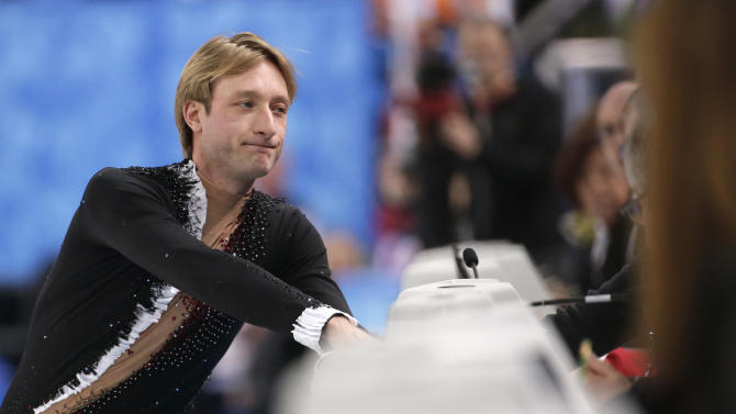 Evgeni Plushenko of Russia speaks with an official prior to pulling out of the men's short program figure skating competition due to illness at the Iceberg Skating Palace during the 2014 Winter Olympics, Thursday, Feb. 13, 2014, in Sochi, Russia. (AP Photo/Bernat Armangue)