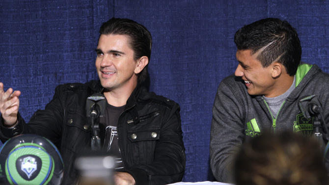 "Seattle Sounders FC forward Fredy Montero, right, smiles as he looks on during a news conference with Latin superstar musician Juanes about Juanes upcoming tour Tuesday, March 8, 2011, in Seattle. Juanes kicks-off his world ""P.A.R.C.E. Tour"" Thursday March 10, in Seattle. (AP Photo/Elaine Thompson)"