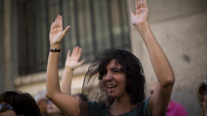 Civil servant Maria Jose Rodriguez, wearing a veils as if she were at a funeral, rises her hands and shouts slogans condemning the recent austerity measures announced by the Spanish government, during a demonstrations in Madrid, Spain, on Friday July 13, 2012.  Spanish civil servants, some dressed in the black of mourning, took to the streets Friday to protest their second wave of wage cuts in as many years as the government prepared to approve austerity measures that include those reductions as part of a deficit-cutting plan to save euro 65 billion through 2015. (AP Photo/Emilio Morenatti)