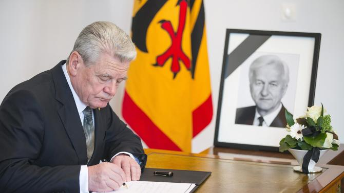 German President Joachim Gauck writes in a condolence book for late former president Richard von Weizsaecker, in Berlin