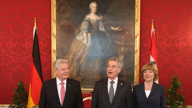 Austrian President Heinz Fischer, center, welcomes German President Joachim Gauck. left, and  Gauck's partner Daniela Schadt, right, for talks at the Hofburg palace in Vienna, Austria, Monday, April 27, 2015. Painting in the background shows late Austrian Empress Maria Theresia. (AP Photo/Ronald Zak)