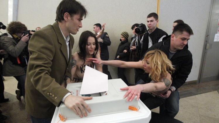 "Polling station officials clash with topless members of Ukrainian feminist group FEMEN members at a polling station in Moscow on Sunday, March 4, 2012. Written on the bodies of the radically anti-Putin protesters is the slogan ""I steal for Putin"", referring to their symbolic act of trying to steal votes.  Polling stations have opened across Russia's vast expanse for the presidential election widely expected to return Vladimir Putin to the Kremlin. (AP Photo/Misha Japaridze)"
