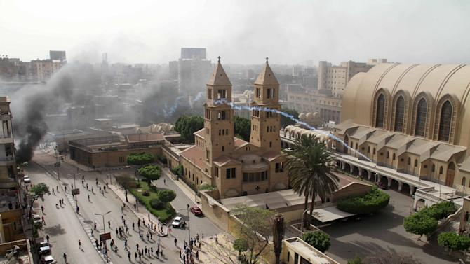 A tear gas canister is fired by Egyptian riot police into the compound of the Coptic Orthodox Cathedral after the funeral of four Christians killed in sectarian clashes near Cairo over the weekend in Cairo, Egypt, Sunday, April 7, 2013. Attacks against Christians, who make up about 10 percent of Egypt's estimated 90 million people, have increased since President Morsi's Muslim Brotherhood came to power last year. (AP Photo/Mostafa El Shemy)