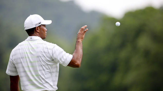 Tiger Woods catches a ball from his caddy during The Greenbrier Classic PGA Golf tournament in White Sulphur Springs, W.Va., Thursday, July 5, 2012. Woods finished the day at 1-over 71.  (AP Photo/The Roanoke Times, Kyle Green)