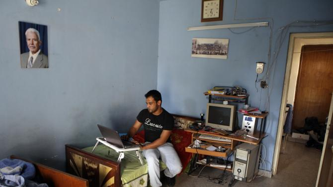 Hussein Ibrahim al-Tikriti works on a laptop at his home in Baghdad, Iraq, Tuesday, July 26, 2011. Al-Tikriti, a native of Saddam Hussein's hometown and a translator for American and British security companies, hoped to find safety by moving to the United States under a program designed to help Iraqis who've risked their lives for the U.S. government. But like many other would-be refugees, al-Tikriti has been stuck in limbo amid a sharp tightening in security checks for entry to the United States. (AP Photo/Khalid Mohammed)