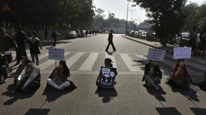 """Indian protesters hold placards as they block a major traffic intersection during a protest in New Delhi, India, Wednesday, Dec. 19, 2012. The hours-long gang-rape and near fatal beating of a 23-year-old student on a bus in New Delhi triggered outrage and anger across the country Wednesday as Indians demanded action from authorities who have long ignored persistent violence and harassment against women. The placards read as, left, """"Give harsh punishment to the culprits,"""" second from right, """"Delhi government: Protect women.""""  (AP Photo/Altaf Qadri)"""