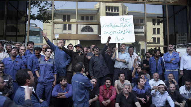 In this Tuesday, Aug. 14, 2012 photo, a group of Iranian workers protest in front the Industrial Ministry building in Tehran, Iran, demanding their delayed salaries. For weeks, a manifesto complaining about Iran's sinking economy circulated in secret among factories and workshops. In the end, some 10,000 signatures were on a petition addressed to Iran's labor minister calling attention to the street-level fallout from Western sanctions: rising prices, fewer jobs. (AP Photo)