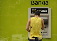 A man uses a Bankia ATM machine n Madrid. Spain has charged two global consulting firms, Roland Berger and Oliver Wyman, with valuing the battered banking system's deeply troubled balance sheets