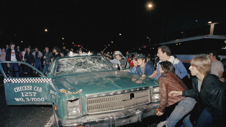 FILE - In this Oct. 14, 1984 file photo, a crowd attempts to topple a damaged taxi car outside Detroit's Tiger Stadium after the Detroit Tigers defeated the San Diego Padres to win the 1984 World Series baseball championship. (AP Photo)