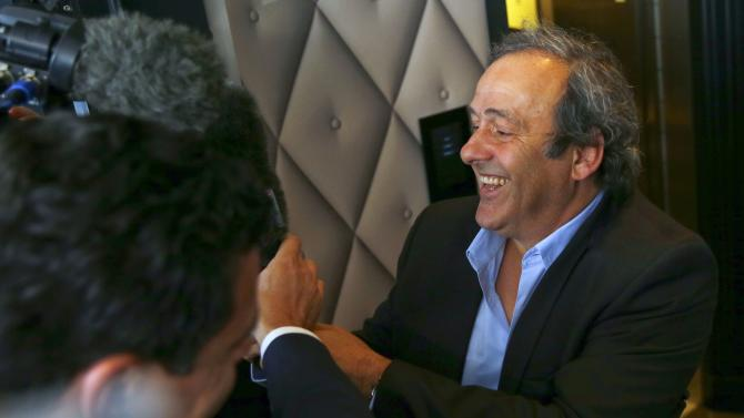 UEFA President Platini grabs a microphone as a joke at his arrival for a meeting in Zurich