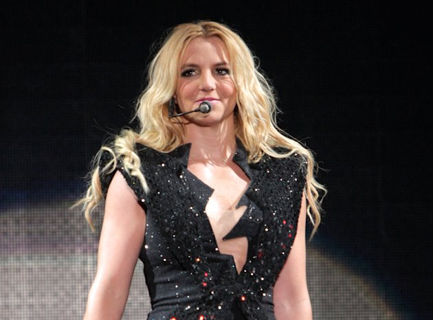 FILE - In this Sept. 27, 2011 file photo, singer Britney Spears performs on a stage during a concert in Kiev, Ukraine, during her European Femme Fatale Tour. A source says she is joining Simon Cowell'