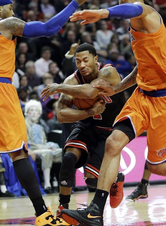 Chicago Bulls guard Derrick Rose, center, drives to the basket between New York Knicks forward Carmelo Anthony, left, and center Tyson Chandler during the second half of an NBA basketball game in Chic