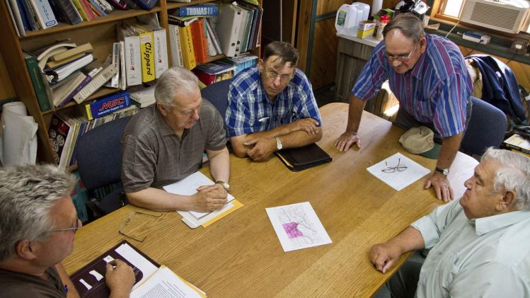 "A group of 5 ""Secession Committee"" members look over maps and discuss details of the proposed secession territory of Lyndon during a meeting in Caribou"