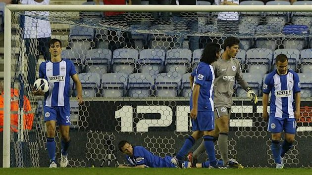 Wigan players react to defeat at home to Swansea (AFP)