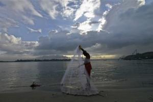 A fisherman arranges his fishing net at a beach against the backdrop of pre-monsoon clouds in Kochi