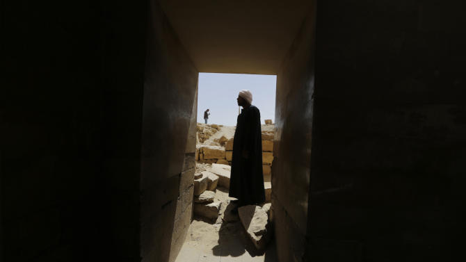 An Egyptian archeology worker stands at the gate of the temple of Saqqara that serves as an entrance to the Djoser Pyramid, 30 kilometers southwest of Cairo, in Saqqara, Egypt, Sept. 16, 2014. The restoration of the 4,600-year old pyramid has prompted controversy between the Ministry of Antiquities, activists and archaeologists. (AP Photo/Amr Nabil)