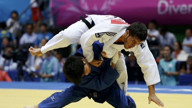 Japan's Toru Shishime competes with Uzbekistan's Sharafuddin Lutfillaev during their men's -60kg bronze medal judo match during the 17th Asian Games in Incheon