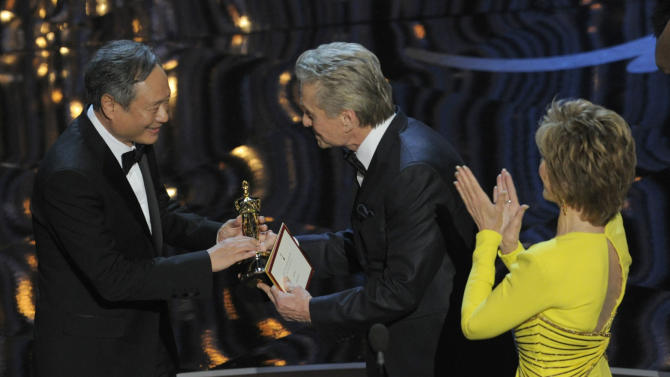 """Presenters Jane Fonda, right, and Michael Douglas present the award for best directing to Ang Lee for """"Life of Pi,"""" left, during the Oscars at the Dolby Theatre on Sunday Feb. 24, 2013, in Los Angeles.  (Photo by Chris Pizzello/Invision/AP)"""