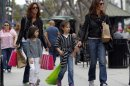 In this April 24, 2012, file photo, women and girls carry purchases on the Third Street Promenade in Santa Monica, Calif. The Commerce Department said Friday, April 27, 2012, that the economy expanded at an annual rate of 2.2 percent in the January-March quarter, compared with a 3 percent gain in the final quarter of 2011. Consumers spent at the fastest pace in more than a year. (AP Photo/Reed Saxon, File)