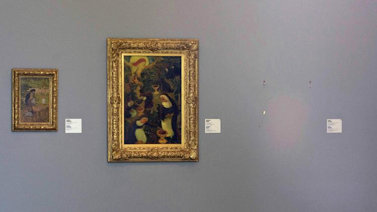 """FILE - In this Oct. 16, 2012 file photo, the empty space where Henri Matisse' painting """"La Liseuse en Blanc et Jaune"""" was hanging, right, is seen next to a painting by Maurice Denis, center, and Pierre Bonnard, left, at Kunsthal museum in Rotterdam, Netherlands. If Rotterdam's stunning heist of Picasso, Monet and Matisse paintings last month focused attention on the murky world of art theft, Ghent's gothic Saint Bavo cathedral has been at the center of a crime that has bedeviled the art world for decades. The Just Judges panel of the Van Eyck brothers' multi-panel Gothic masterpiece hasn't been seen since 1934, when chief suspect Arsene Goedertier suffered a stroke at a political rally close to Ghent and died after murmuring possibe clues to the crime to a  confidant. (AP Photo/Peter Dejong, File)"""