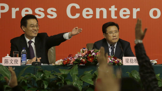 """Moderator Chen Wenjun, left, invites questions from reporters next to Liang Wengen, Chairman of the board of the SANY Group at a press conference with the theme of """"implementing innovation strategies to accelerate transformation and development"""" as part of the 18th Communist Party Congress at the media centre in Beijing, Saturday, Nov. 10, 2012. (AP Photo/Ng Han Guan)"""