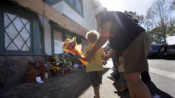 Aidan Smith, 5, walks to place flowers in front of Salon Meritage where eight people were killed in Wednesday's shooting rampage in Seal Beach, Calif., Thursday, Oct. 13, 2011. The ex-wife of the man suspected of killing eight people in a shooting rampage at a hair salon claimed in court papers filed this year that he was mentally unstable and had threatened to kill himself or someone else at least once. (AP Photo/Jae C. Hong)